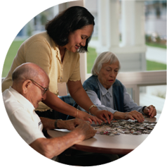 Picture of elderly people doing a jigsaw with a care assistant